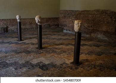ITALY,BRESCIA -26 June 2019:Brixia Archaeological Park of Brescia Romana. From left: head of Minerva white marble, head of Minerva white marble, head of Silenus white marble.Floor: geometrical marble