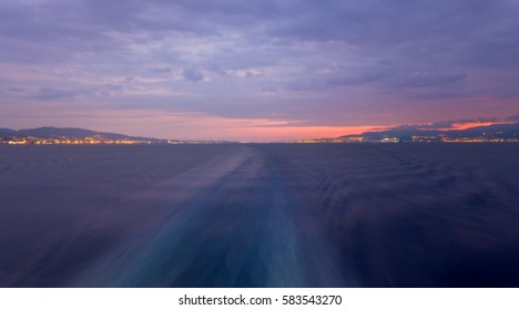 Italy's narrow and busy Strait of Messina, separating Sicily and Calabria, during a cloudy sunrise