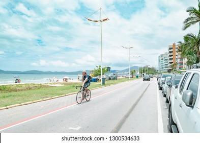 Itapema - SC, Brazil - December 26, 2018: Seaside avenue Avenida Beira Mar. Buildings of the city on a street in seafront, Meia Praia Itapema beach. Touristy beach town.