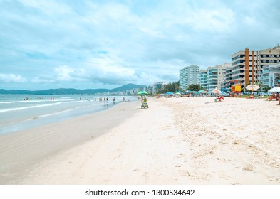 Itapema - SC, Brazil - December 26, 2018: People at Meia Praia Itapema beach. Touristic beach during high season, bathers on the sand in front of the sea, beautiful summer day.