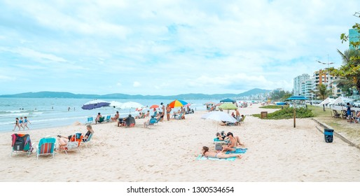 Itapema - SC, Brazil - December 26, 2018: Panoramic view of Meia Praia Itapema beach. Touristic beach during high season, bathers on the sand in front of the sea, beautiful summer day.