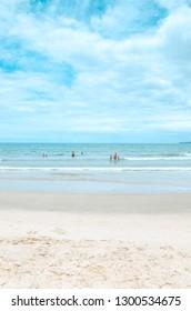 Itapema - SC, Brazil - December 26, 2018: People at Meia Praia Itapema beach. Touristic beach during high season, bathers on the sea, beautiful summer day.