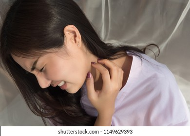 itching woman scratching her neck skin; portrait of asian woman suffering from rash, skin infection, skin allergy, bacteria or ringworm or fungus infection; 20s young adult asian woman model