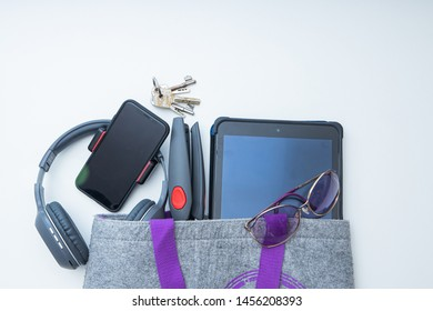 The item in the bag when poured out are bluetooth headphones , mobile tripods, notebook, sunglasses and home keys. White background