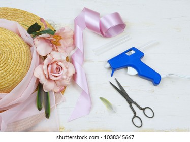 Items to decorate a bonnet includes a straw hat, vintage scissors, silk roses and a glue gun on a rustic wooden background. The color is a soft pink. Good for a wedding or as a Kentucky Derby hat.