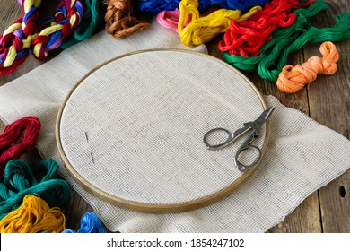 Items for embroidery. Hoop, colorful floss threads and canvas on old wooden background