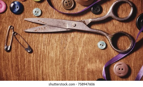 Items for embroidery scissors and buttons on a wooden background