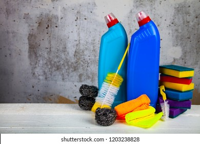 Items for home or office cleaning on the background of a gray wall.