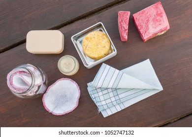 Items necessary for a plastic free, zero waste bathroom. Organic cotton reusable make up removal pads, textile handkerchief, homemade lavender cream, natural soap bars and solid shampoo/conditioner.