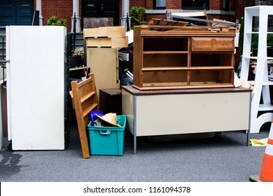 Items and old furniture on street outside house moving day or getting rid of junk and household storage concept