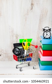Items for school in a shopping trolley,alarm clock and books on a wooden background. Concept of buying items for school. Back to school.