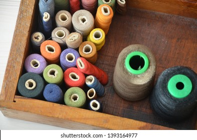 items of sewing. colorful bobbins in the wooden box