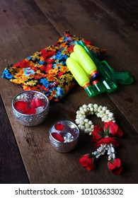 Items for Songkran (Thai Water Festival) on wood : Rose and jasmine garland, traditional silver blessing bowl of water, colorful clothes with flower design and water gun.