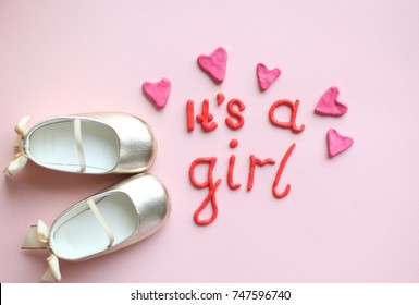 """""""It's a girl"""" lettering with plasticine letters on pink background top view, first baby shoes or baby steps with plasticine hearts"""