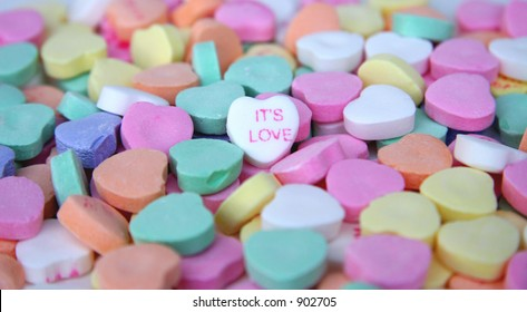 """Its Love"" candy heart surrounded by other candy hearts."
