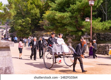 Itsukushima, Japan- september 19, 2018: beautiful newly married couple on a traditional cart pulled by a young man in the beautiful scenery of Itsukushima Island