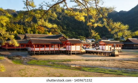 Itsukushima Shinto shrine at golden hour on Miyajima Island in Japan. The Shinden architectural style complex is built on stilts by the sea, so the shrine appears to be floating at high-tide.