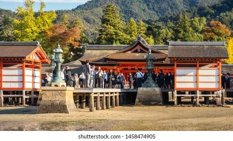 Itsukushima Shrine, Miyajima, Japan - November 7, 2018: Tourists walk around the main temple at Itsukushima Shrine on Miyajima island famous for the floating Torii gate in Hiroshima bay, Japan.