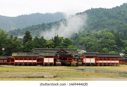 The Itsukushima Shrine Takabutai  at low tide standing in front of misty and forested mountains on Miyajima Island near Hiroshima.