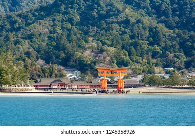 """Itsukushima Shrine torii with plaque writing """"Itsukushima Shrine"""" in Kanji character surrounded by tourists during low tide with other structures of Itsukushima Shrine in the background"""