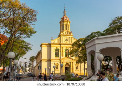 Itu São Paulo Brazil - October 5th 2020: People with mask enjoying Sunday late afternoon in the square with historic church in the background