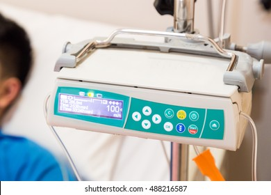 IV infusion pump regulator in hospital with patient at background