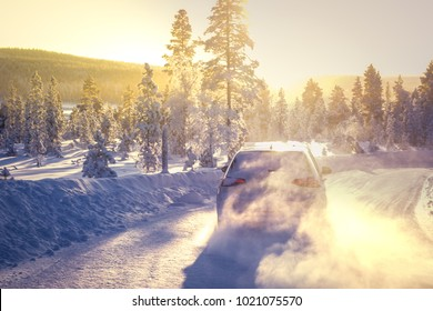 IVALO, FINLAND - February 4, 2018: White hatchback car VW Golf drives fast on a snowy winding road in Lapland during a sunny day. Naturally blurred winter forest background. Focus on a side of a car.