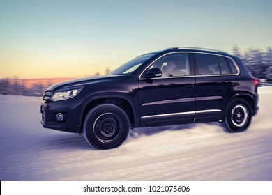 IVALO, FINLAND - February 4, 2018: Black SUV VW Tiguan accelerates on a flat snow surface in Lapland during a sunny day. Naturally blurred winter forest background. Color toning applied.