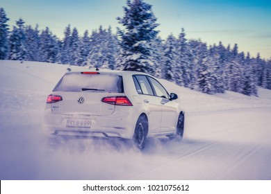 IVALO, FINLAND - February 4, 2018: White hatchback car VW Golf brakes on a flat snow surface in Lapland during a sunny day. Naturally blurred winter forest background. Color toning applied.