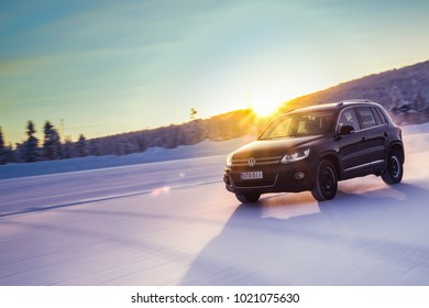 IVALO, FINLAND - February 4, 2018: Black SUV VW Tiguan drives on a  flat snow surface in Lapland. Bright sunlight glare in a background. Color toning applied in post-production.