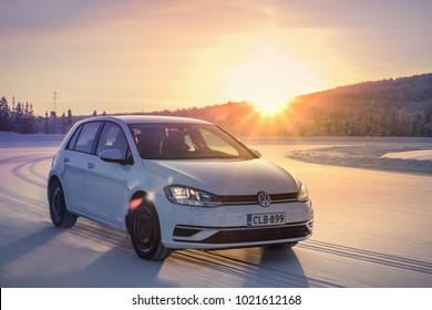 IVALO, FINLAND - February 4, 2018: White hatchback car VW Golf drives on a flat snow surface in Lapland. Bright sunlight glare in a background. Color toning applied in post-production.