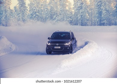IVALO, FINLAND - February 4, 2018: Black SUV VW drives fast on a winding snowy road in Lapland during a sunny day. Naturally blurred winter forest background.