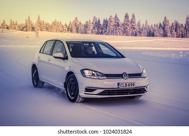 IVALO, FINLAND - February 4, 2018: White hatchback car Volkswagen Golf drives on a flat snow surface in Lapland during a sunny day. Winter forest background.  Color toning applied.
