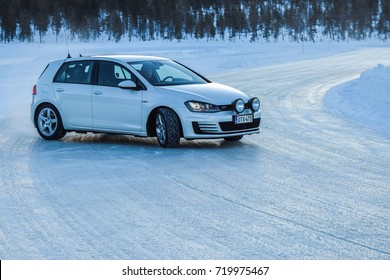 IVALO, FINLAND - January 21, 2017: Winter tire test is held at the proving ground. Test car Volkswagen Golf GTI drives on a track made on a frozen lake with studded tyres on.
