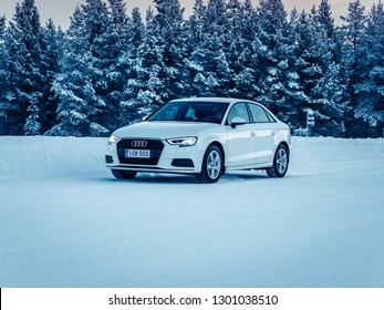 IVALO, FINLAND - January 23, 2019: White Audi A3 Sedan accelerates on a flat snow surface in Lapland during a cloudy day. Naturally blurred winter forest background. Some color toning applied.