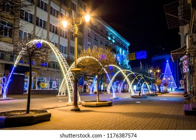 Ivano-Frankivsk city, Ukraine - 1 January 2018: Night view of New Year or Christmas decorative arches with bright lights during winter holidays