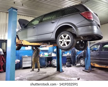 Ivano-Frankivsk, UKRAINE - December 25, 2019: Automobile workshop interior. Master mechanic checking suspended car. Vehicle diagnostics and maintenance.