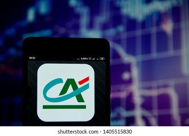 Ivano-Frankivsk, Ukraine - May 22, 2019: Credit Agricole logo is seen on an smartphone over stock chart. Credit Agricole logo is displayed on the screen of a mobile device.
