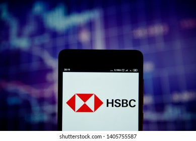 Ivano-Frankivsk, Ukraine - May 22, 2019: HSBC logo is seen on an smartphone over stock chart. HSBC logo is displayed on the screen of a mobile device.