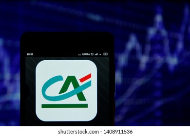 Ivano-Frankivsk, Ukraine - May 22, 2019: Crédit Agricole logo is seen on an smartphone over stock chart. Crédit Agricole logo is displayed on the screen of a mobile device.