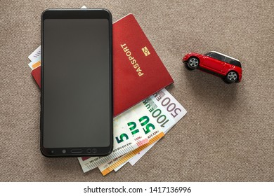 Ivano-Frankivsk, Ukraine - May 6, 2019: Black cellphone, money euro banknotes bills, passport and toy car on copy space background. Travel light, comfortable journey vacation planning concept.