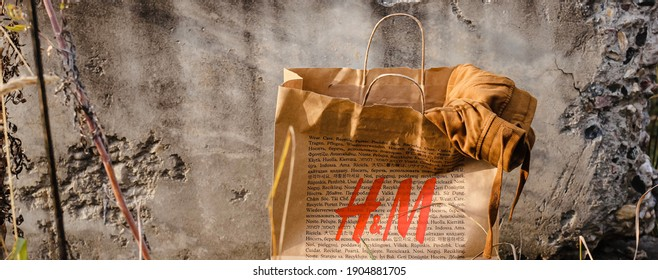 Ivanovo, Russia - October 4, 2020: H and M (international chain of mass fashion retail clothing stores) paper eco friendly shopping bag staying on natural background. Brand refused using plastic bags.