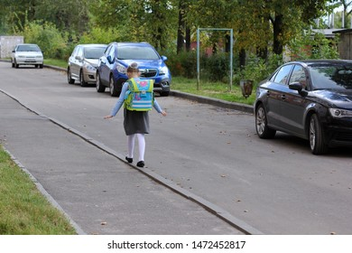 Ivanovo, Russia - September 2015: pretty girl in school uniform walking on the curb balancing hands. Schoolgirl with a backpack goes from school. Back to school concept. Sunny day. Residential area.