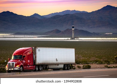 Ivanpah, CA. / USA - April 18, 2019: An oil and diesel powered truck with solar power plant in the background, clean thermal energy versus fossil fuels