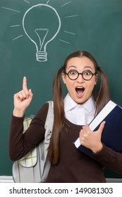 I've got an idea! Surprised young women pointing with her finger while standing in front of the blackboard