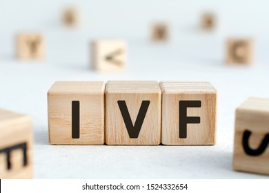 IVF - acronym from wooden blocks with letters, abbreviation IVF In vitro fertilisation concept, random letters around, white  background