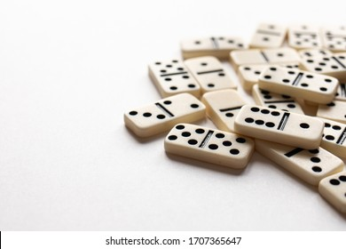 Ivory dominoes in a pile with a white background.