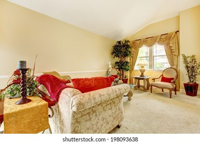 Ivory living room with high vaulted ceiling and carpet floor. Furnished with antique sofa and chairs