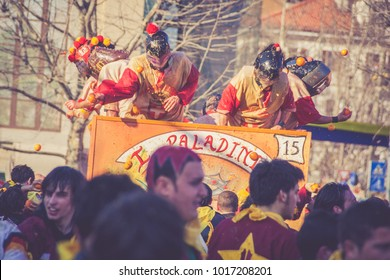 IVREA, ITALY - FEBRUARY 15 2017: Masked people protected with traditional helmets throwing oranges during the traditional Carnival parade of Oranges in the piazza squares