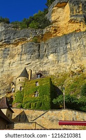 An ivy covered old house with turret below a cliff at Roque-Gageac in France